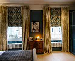 master bedroom with designer curtains and traditional chest of drawers