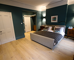 master bedroom with modern coving and wooden flooring