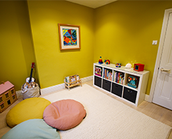 tidy playroom area with mustard yellow wallpaper